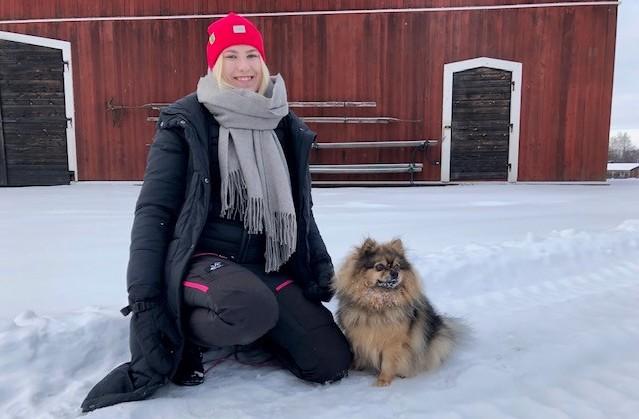 Eerika Mirtola tillsammans med sin kleinspitz Bonzo ute i snön